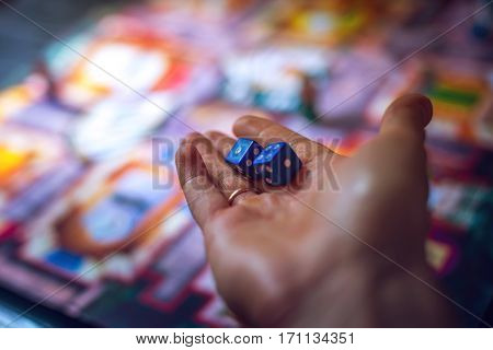 Hand throws the dice on the background of colorful blurred fantasy Board games gaming moments in dynamics