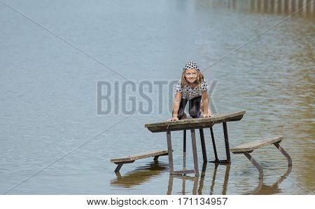 amazing beautiful view of funny happy joyful little girl seating on picnic table standing in lake water
