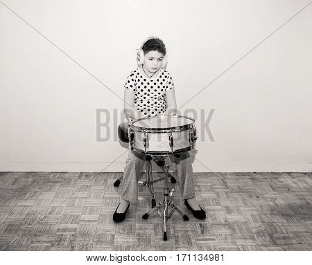 great amazing monochrome view of lonely upset, bored little girl sitting in old studio room behind the snare drum and looking down