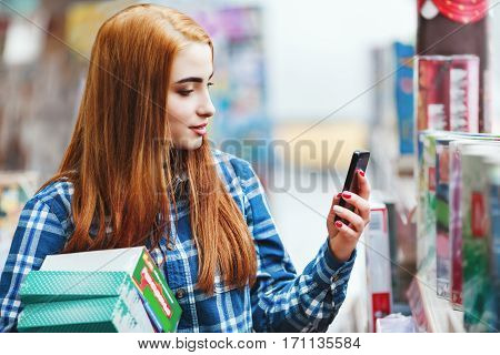 Attractive young girl with long brown hair wearing blue plaid shirt shopping at store, holding boxes and mobile phone and making photo, copy space.