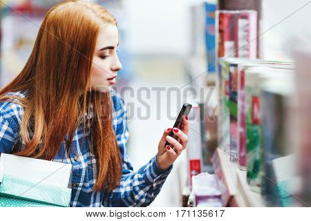 Beautiful young girl with long brown hair wearing blue plaid shirt shopping at store, holding boxes and mobile phone, copy space, making a photo.