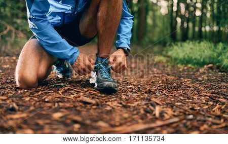 Competitive, athletic young man tightens shoes before running off road outdoors through the woods on a trail in the afternoon wearing sportswear.