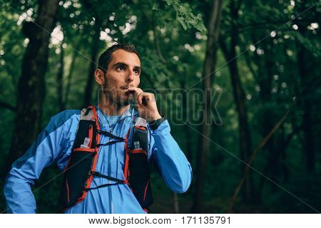 Portait of a competitive, athletic millennial man drinking water from a hydration pack before running off road outdoors through the woods on a trail in the afternoon wearing sportswear.