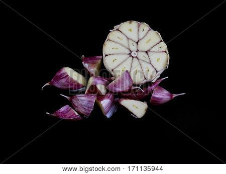Cloves of garlic Allium sativum cut on the cross section on black background