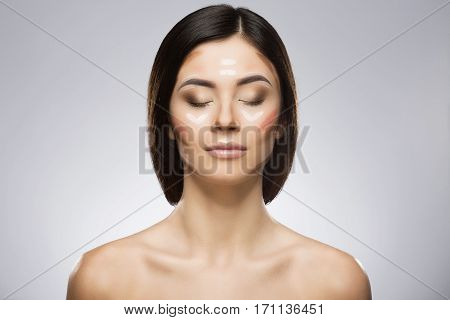 Model with professional contour and highlight face makeup applying sample. Hair at the back, closed eyes. Beauty portrait, head and shoulders, full face. Indoor, studio