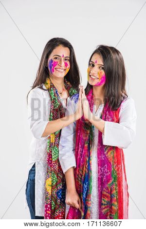 two Indian beautiful girl in namaskar pose or welcoming with hands folded on holi festival, with coloured face, in indian traditional wear and dupatta, isolated over white background with copyspace