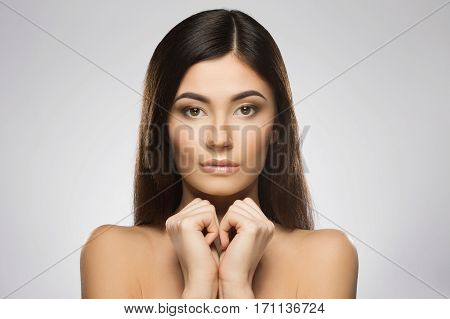 Beautiful girl with nice make-up looking at camera and holding her hands together under chin. Beauty portrait, head and shoulders. Indoor, studio, gray background