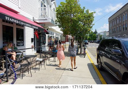 HARBOR SPRINGS, MICHIGAN / UNITED STATES - AUGUST 4, 2016: Pedestrians stroll past the Stained Cup Coffee Company on Main Street in downtown Harbor Springs.