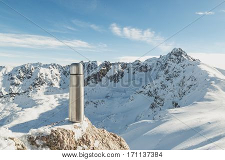 Classical steel thermos in winter in the mountains with mountains in the background.