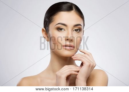 Girl with make-up and ponytail looking at camera. Touching face by one hand. Head turned a little bit aside. Beauty portrait, head and shoulders. Indoor, studio, gray background