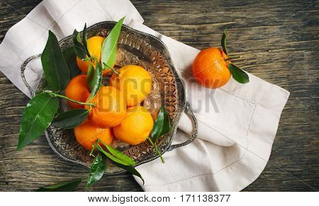 Fresh tangerines with leaves on table top view