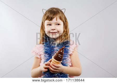 Lovely little girl wearing pink dress, metal cat ears and blue festoon holding an ice-cream, looking right at gray studio background, copy space.