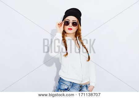 Attractive teenage red-haired girl with long hair wearing white shirt, jeans, black hat and sunglasses, stylish haircut and makeup, red lips.
