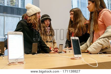 New York February 9 2017: Teenage girls from Europe are having a conversation inside Apple store on 5th Avenue.