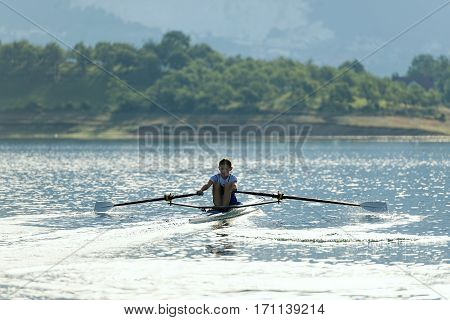 single rower at sunrise at the lake