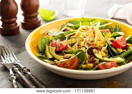 Mexican salad with bacon, corn, tortilla strips and avocado