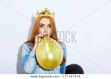 Cute red-haired girl with long hair wearing blue shirt and crown filling a balloon, black manicure, portrait, copy space, white background, fashion photo.