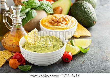 Guacamole and hummus in white bowls with vegetables and corn chips