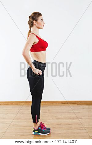 Gorgeous sportive girl wearing snickers, black leggings and red short top standing at gym holding hands on waist, fitness, white wall and wooden floor at background.