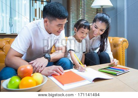 Father and Mather teach and relax with they Daughter to do home work by draw and paint family kid education concept.
