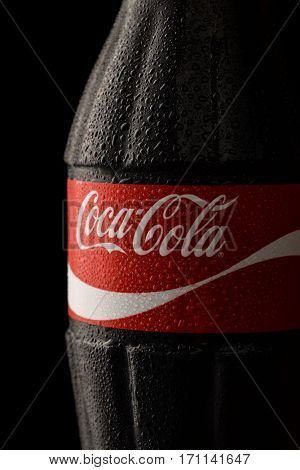 Samara, Russia - February 2017. Close up of Coca-Cola classic bottle with drops on black background