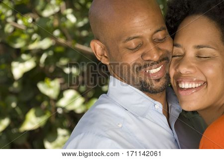 Loving African American couple hugging outside at the park.