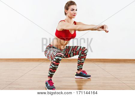 Girl with light brown hair wearing pink sneakers, colorful leggings and red short top doing squatting at gym, white wall and wooden floor, fitness, copy space, portrait.