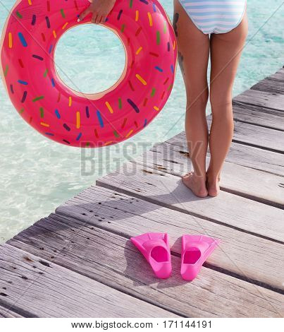 Tropical summer holiday concept, woman with inflatable doughnut ring standing on wooden pier by the beach
