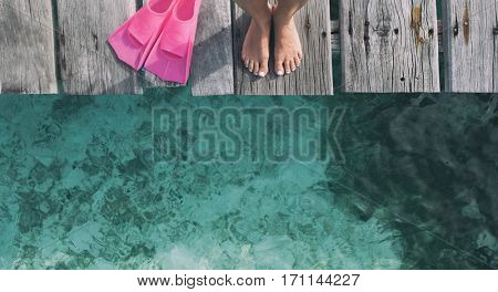 Summer holiday fashion selfie concept - woman feet on a wooden pier at the beach with pink fins flippers