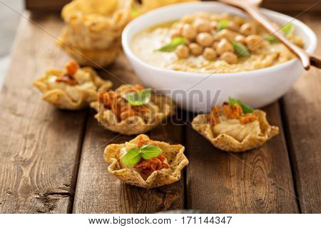 Homemade hummus in tortilla bowls with dried peppers, small appetizers