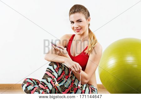 Young with light brown hair wearing gray snickers, colorful leggings and red short top sitting at gym with mobile phone and fitball, fitness, portrait.
