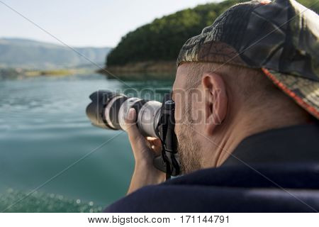 Photographer in nature taking pictures to a beautiful lake.