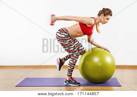 Nice girl with light brown hair wearing gray snickers, colorful leggings and red short top doing exercises with fitball on purple matt at gym, holding pink dumbbell.