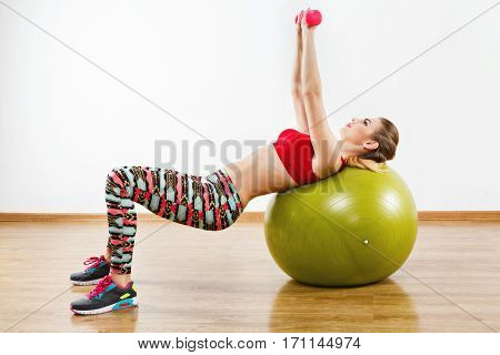 Young girl with light brown hair wearing gray snickers, colorful leggings and red short top doing exercises with fitball at gym, holding pink dumbbells, fitness, portrait.