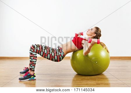 Girl girl with light brown hair wearing gray snickers, colorful leggings and red short top doing exercises with fitball at gym, holding pink dumbbells, white background.