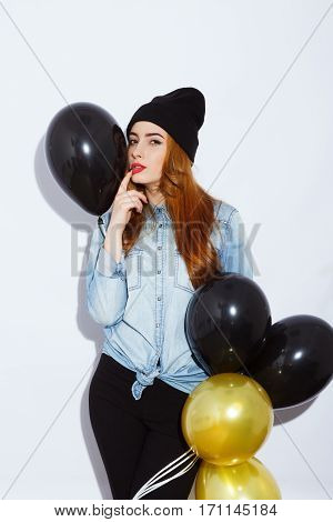 Girl teenage red-haired girl with long hair wearing blue shirt and hat holding black and golden balloons, red lips, black manicure, portrait, copy space.