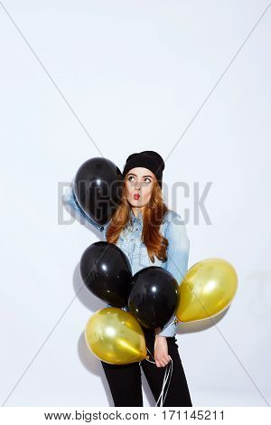 Beautiful teenage red-haired girl with long hair wearing blue shirt and hat holding black and golden balloons, red lips, black manicure, portrait, fashion style.