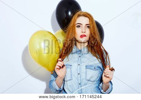 Nice red-haired girl with long hair wearing blue shirt biting her lip and touching hair, black and golden balloons at background, red lips, black manicure, portrait.