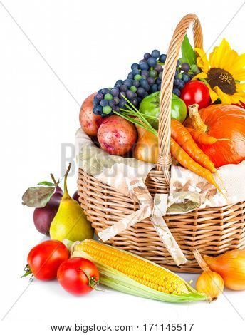 Autumnal harvest vegetable and fruit in basket isolated on white background