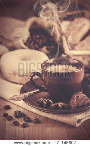 Cup fragrant hot coffee with bean chocolate sweet and loaf in vintage rustic style cinnamon steam smoke on wooden board for bracing morning breakfast