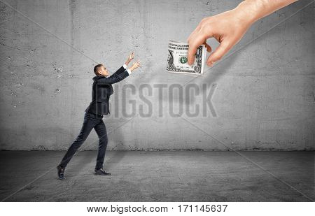 Small businessman on concrete background reaching out for a giant hand holding money. Business and success. Gains and profits. Earning and spending money.