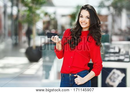 Girl standing in shopping mall, looking at camera and smiling. Beautiful girl holding phone in one hand and another hand on jeans. Wearing red blouse and jeans. Indoor, incidental people