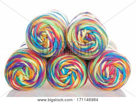 Skeins of rainbow multi colored yarn stacked into a pyramid formation on a reflective white surface isolated on a white background.