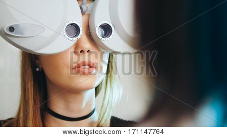 Ophthalmology clinic - woman checks vision by modern equipment - eyes exam, telephoto