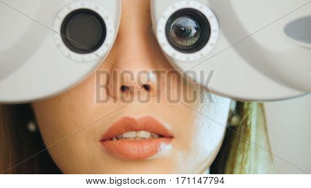 Ophthalmology clinic - woman checks vision by modern equipment - left eye, telephoto