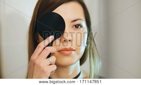 Young female checks vision in ophthalmology clinic, telephoto