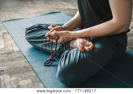 Man's hands man's hands holding string and sitting in lotus asana, yoga position.
