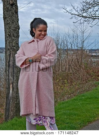 This pretty multi-ethnic woman is in a playful pose wearing a long pastel pink coat outsdoors on an early spring day. Background is the ocean which is intentionally blurred to emphasize subject. Photo is vertical orientation.