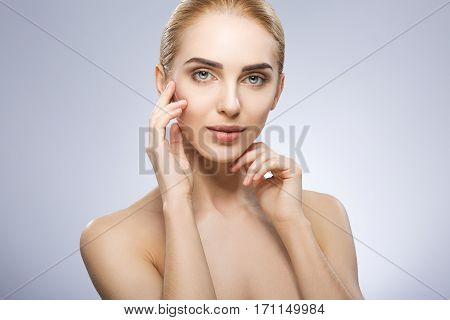 Young girl with light fixed hair behind, blue big eyes and naked shoulders looking at camera and holding hands near face, beauty photo, portrait, copy space.