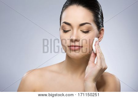 Attractive girl with black fixed hair behind, closed eyes and naked shoulders, cleaning face with cotton pad at gray studio background, portrait, close up.